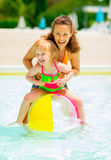 Mother and baby playing with beach ball in pool. Portrait of happy mother and baby girl playing with beach ball in pool Royalty Free Stock Photos