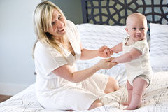 Mother and baby playing on bed Royalty Free Stock Photos