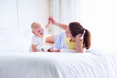 Mother and baby playing in bedroom Stock Photography