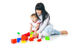 Mother and baby playing with building blocks toy. On white stock photo