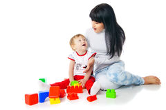 Mother and baby playing with building blocks toy. On white royalty free stock photography