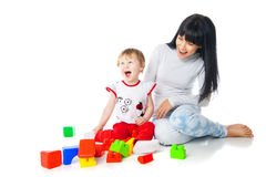 Mother and baby playing with building blocks toy. On white royalty free stock images