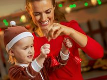 Mother and baby playing with christmas bells Royalty Free Stock Photos