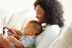 Mother And Baby Playing With Digital Tablet At Home Royalty Free Stock Photo