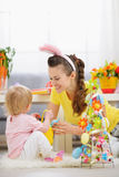 Mother and baby playing with Easter decoration Royalty Free Stock Photos