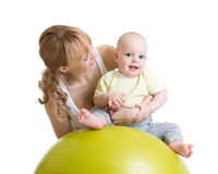 Mother and baby playing with fitness ball. Mother and baby boy playing with fitness ball Royalty Free Stock Images