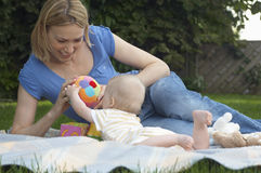 Mother And Baby Playing On Lawn stock photos
