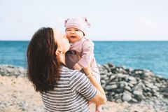 Mother and baby playing outdoors on sea beach. stock images