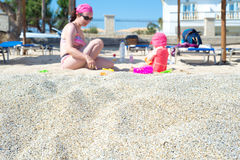 Mother and baby playing in the sand. Focus on sand Royalty Free Stock Photo