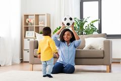 Mother and baby playing with soccer ball at home. Childhood, kids and people concept - happy african american mother and her baby son playing with soccer ball stock photos