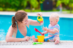 Mother and baby playing in swimming pool Stock Image