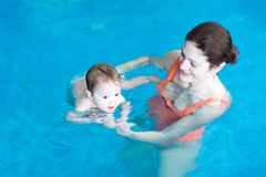Mother and baby playing in a swimming pool. Mother and little baby playing in a swimming pool stock photos