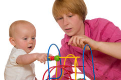 Mother and baby playing together. Attractive young mother and her small baby playing together with a colourful educational toy consisting of a frame with movable Stock Image