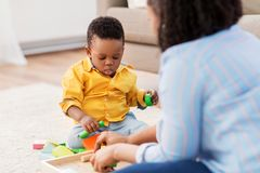 Mother and baby playing with toy blocks at home. Childhood, kids and people concept - african american mother and her baby son playing together with wooden toy royalty free stock images