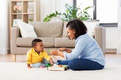 Mother and baby playing with toy blocks at home. Childhood, kids and people concept - happy african american mother and her baby son playing together with wooden stock photos