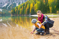 Mother and baby playing with water on lake braies Royalty Free Stock Images