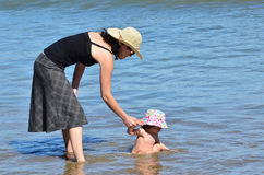 Mother and baby plays in the sea Stock Images