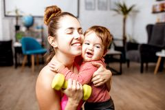 Mother and baby portrait during the exercise. Portrait of a mother with her cute baby son hugging together during the exercise at home royalty free stock photo
