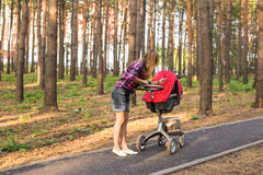 Mother with baby in pram walking in summer park Royalty Free Stock Images