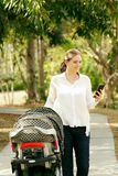 Mother With Baby In Pushchair Sending Message On Phone Royalty Free Stock Image
