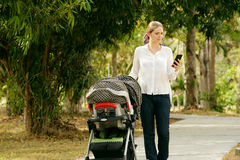 Mother With Baby In Pushchair Typing Message On Phone Stock Photos
