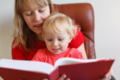 Mother baby reading. Mother and baby reading book while sitting in chair Royalty Free Stock Photography