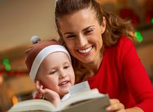 Mother and baby reading book in christmas decorated kitchen Royalty Free Stock Photo