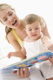 Mother and baby reading book indoors Stock Photography