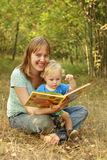 Mother and baby reading book in nature Royalty Free Stock Photography