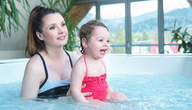Mother and baby relaxing in a small swimming pool Stock Photos