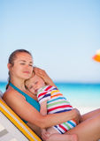 Mother and baby relaxing on sunbed on beach. Mother and baby girl relaxing on sunbed on beach Stock Photography