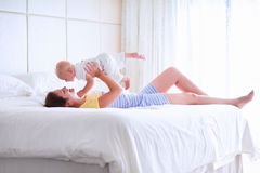 Mother and baby relaxing in white bedroom Stock Image
