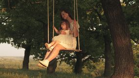 Mother and baby ride on a rope swing on an oak branch in forest. Mom shakes her daughter on swing under a tree in sun stock video footage