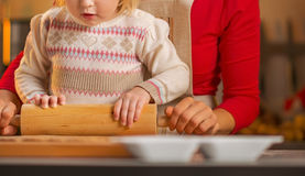Mother and baby rolling pin dough in christmas decorated kitchen Royalty Free Stock Photos