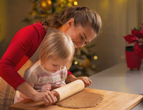 Mother and baby rolling pin dough in christmas decorated kitchen Royalty Free Stock Image