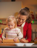 Mother and baby rolling pin dough in christmas decorated kitchen Stock Photos
