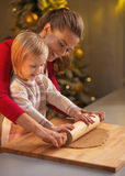 Mother and baby rolling pin dough in christmas decorated kitchen Royalty Free Stock Images