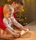 Mother and baby rolling pin dough in christmas decorated kitchen Stock Photography