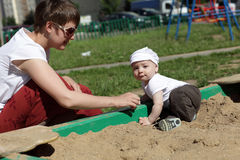 Mother and baby in sandbox. Mother and her baby are in sandbox on playground Royalty Free Stock Images