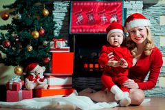 Mother and baby in santa hats near the fireplace Royalty Free Stock Images