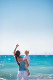 Mother and baby at sea shore pointing up Royalty Free Stock Image