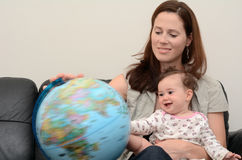 Mother and Baby Search and Examining the Globe Royalty Free Stock Photography