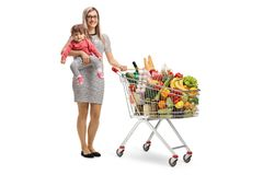 Mother with a baby and a shopping cart with full of products. Full length portrait of a mother with a baby and a shopping cart with full of products isolated on royalty free stock images