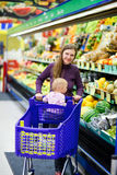 Mother with baby shopping in supermarket Stock Photo