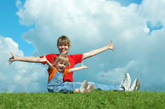Mother and baby sit on grass and open wide hand. Under sky with clouds Stock Photos