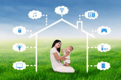 Mother and baby sit under smart house design Royalty Free Stock Image