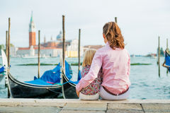 Mother and baby sitting on grand canal embankment Stock Images