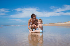 Mother and baby sitting at shore Stock Photos