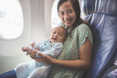 Mother and baby sitting together in airplane Royalty Free Stock Photo