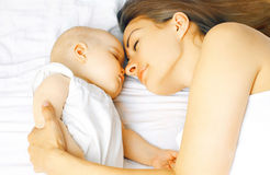 Mother and baby sleep in bed Stock Images